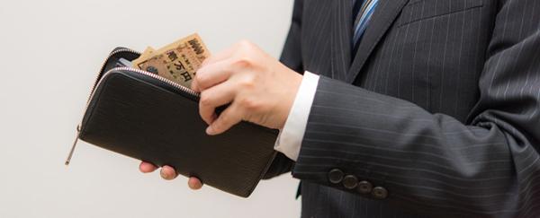 財布から現金を取り出す男性